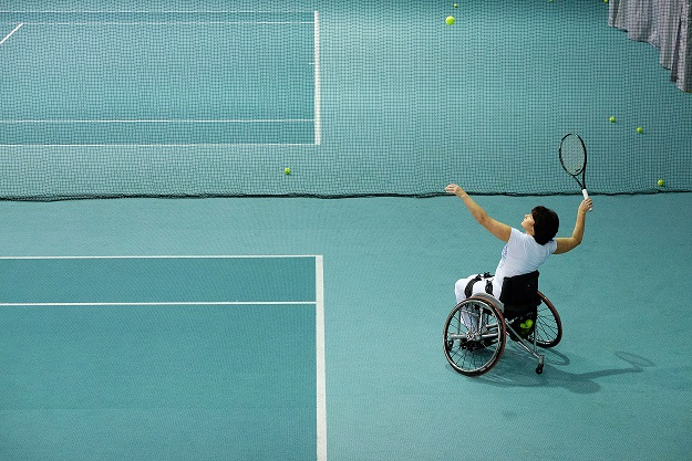 Disabled mature woman on wheelchair playing tennis on tennis court